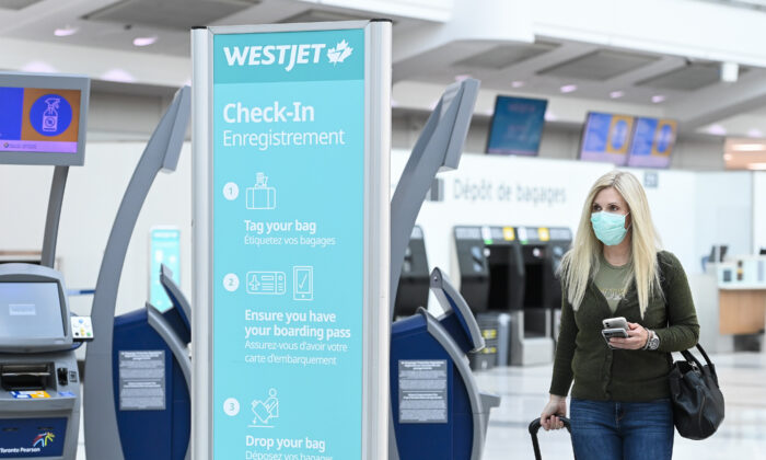 A woman walks through check in at WestJet at Pearson International airport during the COVID-19 pandemic in Toronto on Wednesday, Oct. 14, 2020. Westjet has announced that it will be laying off staff and cutting flights to some cities in Atlantic Canada. (THE CANADIAN PRESS/Nathan Denette)
