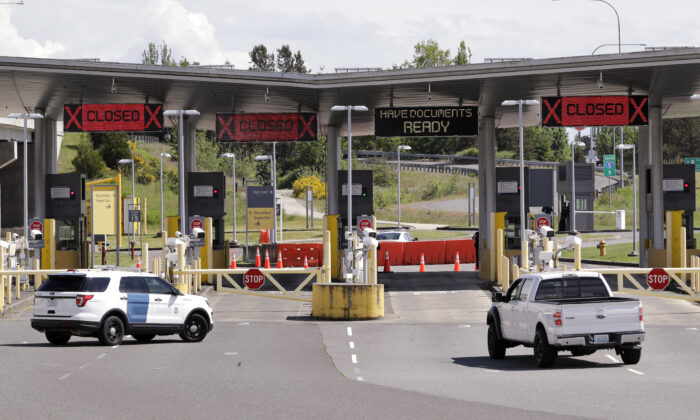 In this photo taken Sunday, May 17, 2020, a truck from Canada heads to the single open lane heading into the U.S. at the Peace Arch border crossing in Blaine, Wash. (AP Photo/Elaine Thompson)