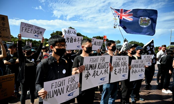 "Supporters of the Hong Kong pro-democracy protesters hold placards during a demonstration as part of the global ""anti-totalitarianism"" movement in Sydney on Sept. 29, 2019. (PETER PARKS/AFP via Getty Images)"