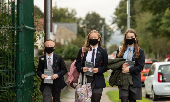 Pupils wearing facemasks as a precaution against the transmission of the CCP virus arrive to attend Moor End Academy in Huddersfield, northern England on Sept. 11, 2020. (Oli Scarff/AFP via Getty Images)