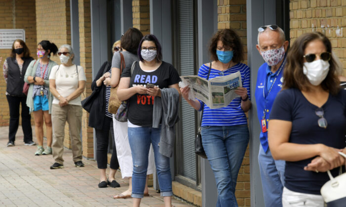 People wait in line at to cast their ballots for the November presidential election on first day of early voting in Alexandria, Va., on Sept. 18, 2020. (John McDonnell/The Washington Post)
