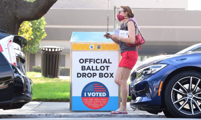 A woman holding her ballot walks past a Vote by Mail Drop Box for the 2020 U.S. Elections in Monterey Park, Calif., on Oct. 5, 2020. (Frederic J. Brown/AFP via Getty Images)