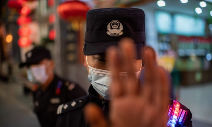A police officer wearing a face mask as a preventive measure against COVID-19 tries to stop a photojournalist from taking pictures on a street outside of a shopping mall complex in Beijing on Oct. 13, 2020. (Nicolas Asfouri/AFP via Getty Images)