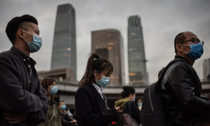 People wearing face masks as a preventive measure against COVID-19 wait at a red light to cross a street during rush hour in Beijing on Oct. 14, 2020. (Nicolas Asfouri/AFP via Getty Images)