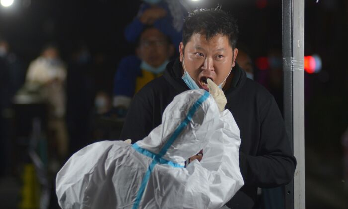 A health worker takes a swab from a resident for COVID-19 nucleic acid test following a new outbreak of the coronavirus in Qingdao, eastern China's Shandong Province on Oct. 13, 2020. (STR/AFP via Getty Images)