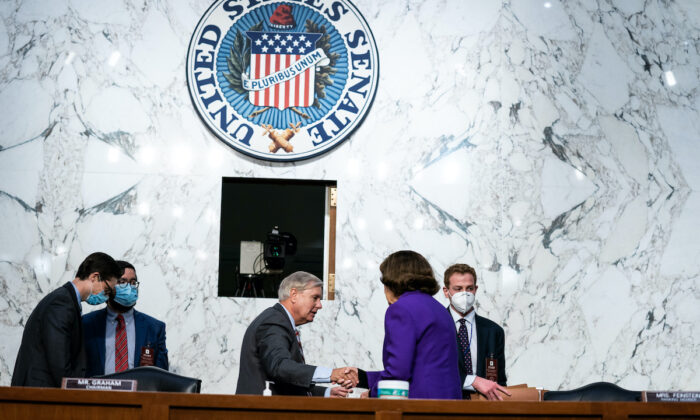 Senate Judiciary Committee Chairman Lindsey Graham (R-S.C.) and Senate Judiciary Committee Ranking Member Dianne Feinstein (D-Calif.) shake hands after the end of the fourth day of Senate Judiciary Committee on the confirmation hearing for Supreme Court nominee Amy Coney Barrett, on Capitol Hill in Washington on Oct. 15, 2020. (Anna Moneymaker-Pool/Getty Images)
