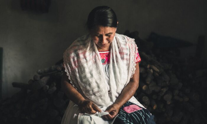 A Mexican artisan in Puebla counts the stitches in her hand embroidery. (Someone Somewhere)