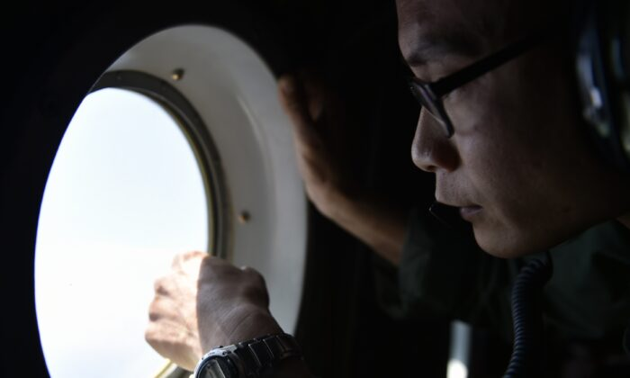 A member of the Taiwan air force looks out a window from a C-130 transport plane during a visit to Taiping Island in the South China Sea on March 23, 2016. (Sam Yeh/AFP via Getty Images)