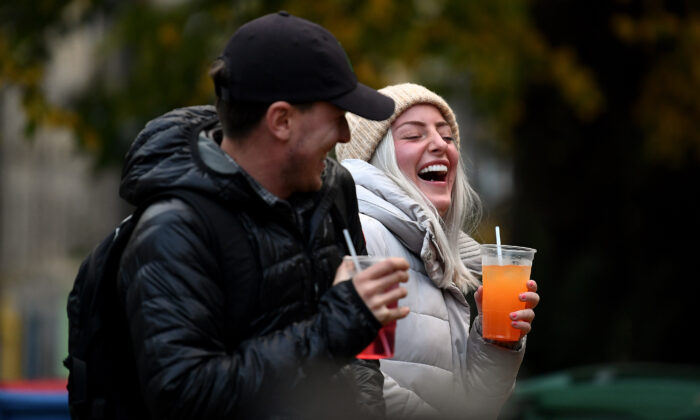 A couple drink from takeaway glasses outside a pub in the Grassmarket following last orders at 6 p.m. in Edinburgh, Scotland, on Oct. 9, 2020. (Jeff J Mitchell/Getty Images)