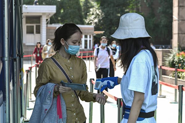 A student (L) has her temperature checked before entering a school to sit the National College Entrance Examination (NCEE), known as Gaokao, in Nanjing, in China's eastern Jiangsu Province on July 7, 2020. Nearly 11 million stressed-out Chinese students took the country's grueling annual college entrance exam following a month-long coronavirus delay, with inspectors this year checking both for cheaters and fevers. (STR/AFP via Getty Images)