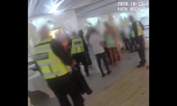A screenshot of a body cam video showing police officers escort people out of an over crowded wedding reception during the CCP virus pandemic, in west London, on Oct. 13, 2020. (Courtesy of MET)