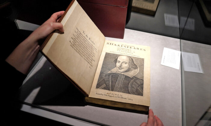 An employee of Christie's auctions holds a 1663 rare first folio of 36 Shakespeare works that was sold for a record 8.4 million dollars (9.978 million with buyers fee) in the Manhattan borough of New York City, New York, U.S., Oct. 14, 2020. REUTERS/Carlo Allegri