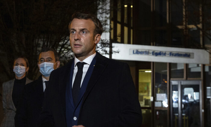 French President Emmanuel Macron, flanked by French Interior Minister Gerald Darmanin, second left, speaks in front of a high school in Conflans Sainte-Honorine, on Oct.16, 2020. (Abdulmonam Eassa, Pool via AP)