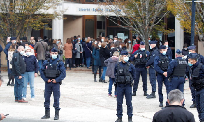 People gather in front of the Bois d'Aulne college after the attack in the Paris suburb of Conflans St Honorine, France, on Oct. 17, 2020. (Charles Platiau/Reuters)