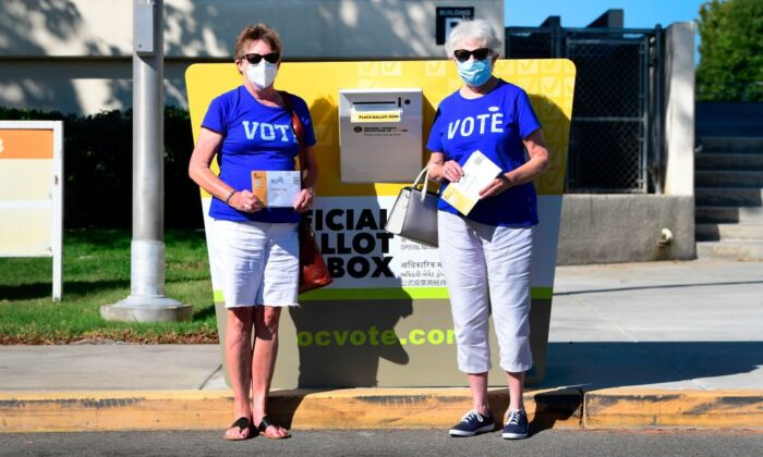 Voters Jeannie Osbourne (L) and Judy Nader (R) stand beside an official Orange County ballot drop box as they prepare to cast their ballots for the 2020 elections at the Orange County Registrar's Office in Santa Ana, Calif., on Oct. 13, 2020. (Frederic J. Brown/AFP via Getty Images)