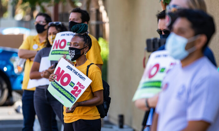 Workers hold signs calling for onlookers to vote against Proposition 22 at a gathering in Orange, Calif., on Oct. 16, 2020. (John Fredricks/The Epoch Times)