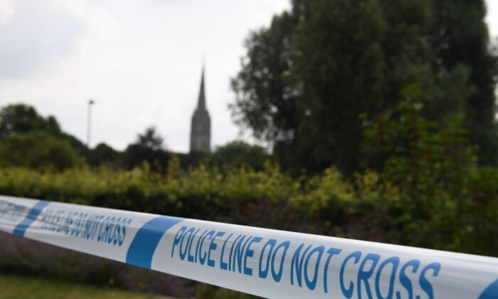 The spire of Salisbury Cathedral is seen behind police tape making a cordon around Queen Elizabeth Gardens, after former Russian spy Sergei Skripal and his daughter Yulia was poisoned, in Salisbury, southern England, on July 5, 2018. (Chris J Ratcliffe / AFP via Getty Images)