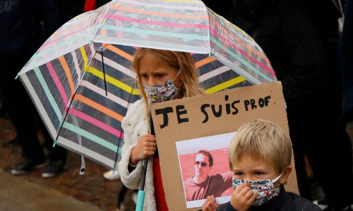 A child holds up a poster of slain French history teacher Samuel Paty, as people take part in demonstrations in support of freedom of speech and in tribute to Paty, on Republique square in Lille, northern France, on Oct. 18, 2020. (Michel Spingler/AP Photo)