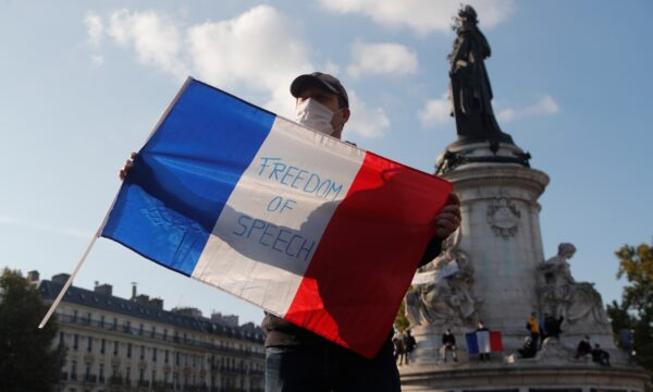 A demonstrator holds a French flag with the slogan _Freedom of Speech_