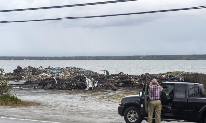 Debris from a burnt out fish plant is scattered along the shore in Middle West Pubnico, N.S., on Oct. 17, 2020. (Andrew Vaughan/The Canadian Press)