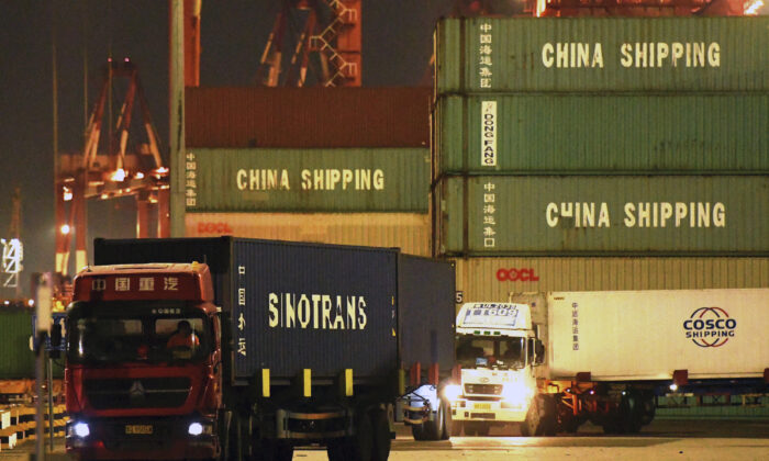 Trucks transport shipping containers at a dockyard in Qingdao in east China's Shandong province on Sept. 25, 2020. (Chinatopix Via AP)