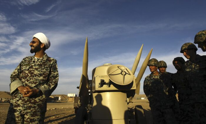 An Iranian clergyman stands next to missiles and army troops, during a manoeuvre, in an undisclosed location in Iran on Nov. 13, 2012. (Majid Asgaripour/Mehr News Agency via AP)
