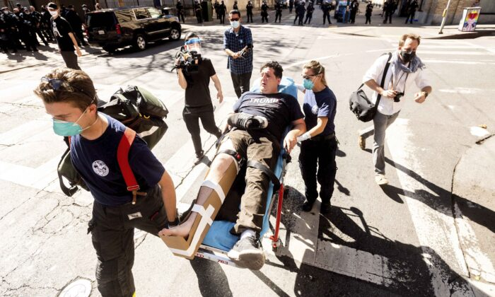 Medics transport a supporter of President Donald Trump to an ambulance after he was attacked by counter-protesters in San Francisco, Calif., on Oct. 17, 2020. (AP Photo/Noah Berger)