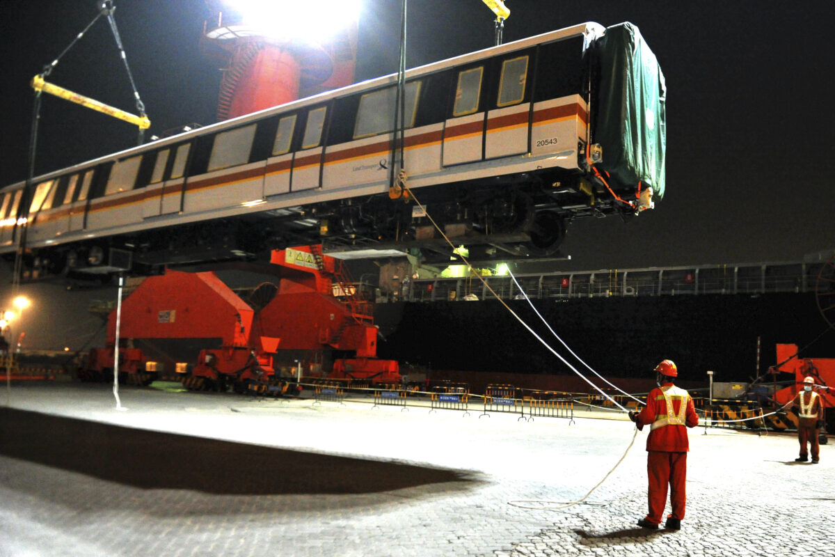 Workers load an exported subway train cartridge