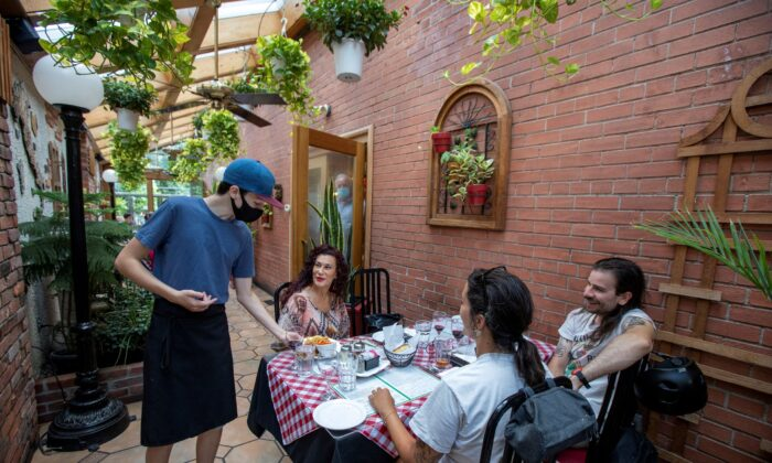A server at Mamma Martino's Restaurant serves customers after indoor dining restaurants, gyms, and cinemas re-open under Phase 3 rules from COVID-19 restrictions in Toronto, on July 31, 2020. (Reuters/Carlos Osorio)