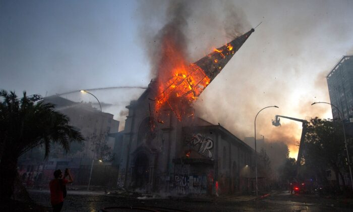 The dome of the church of Asunción falls down burning in flames after being set on fire by rioters on the commemoration of the first anniversary of the social uprising in Chile, in Santiago, on Oct. 18, 2020. (Claudio Reyes/AFP via Getty Images)