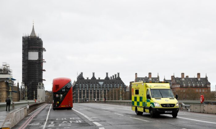 An ambulance drives over Westminster Bridge with the Houses of Parliament in the background in London on April 6, 2020. (Tolga Akmen/AFP via Getty Images)