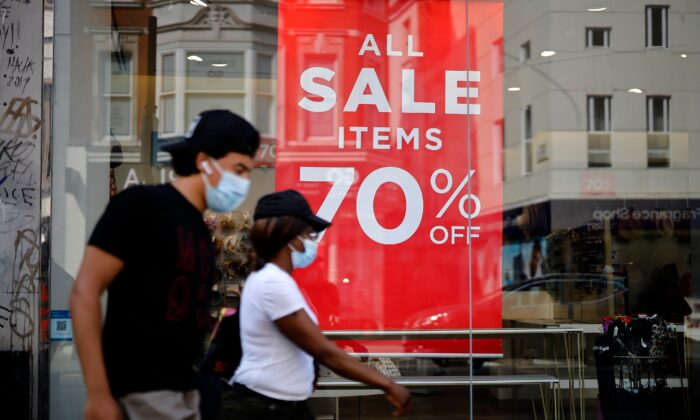 Shoppers wearing face masks walk past sales signs in the window of a shop in London on Aug. 12, 2020. (Tolga Akmen/AFP via Getty Images)
