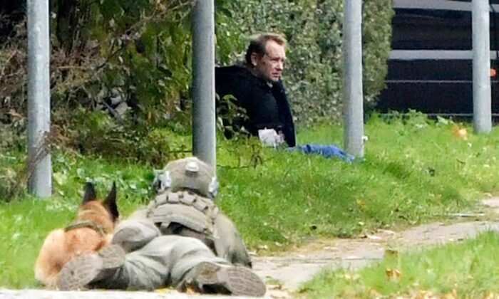 A police officer watches Peter Madsen as he sits on the side of a road after being apprehended following a failed escape attempt in Albertslund, Denmark, on Oct. 20, 2020. The self-taught Danish engineer, who was convicted of torturing and murdering a Swedish journalist on his homemade submarine in 2017 before dismembering her body and dumping it at sea, on Tuesday was captured after an attempted prison escape outside the suburban Copenhagen jail where he is serving life sentence. (Nils Meilvang/Ritzau Scanpix via AP)