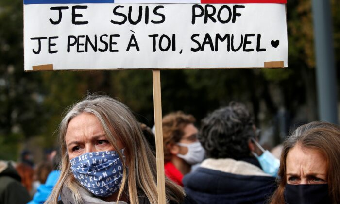 A woman holds a banner as she attends a tribute to Samuel Paty, the French teacher who was beheaded on the streets of the Paris suburb of Conflans St Honorine, at the Place de la Republique, in Lille, France, on Oct.18, 2020. (Pascal Rossignol/Reuters)