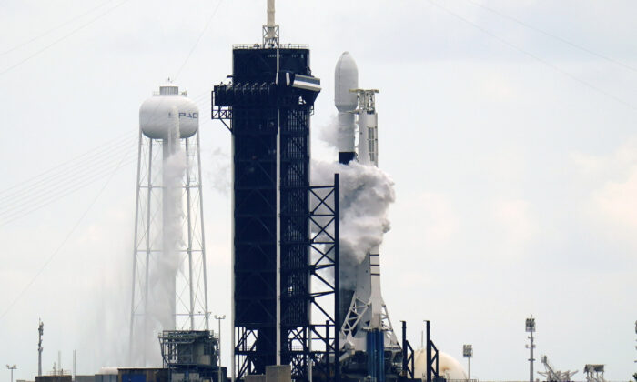 A SpaceX Falcon 9 rocket with a payload of approximately 60 satellites for SpaceX's Starlink broadband network stands on pad 39A moments before the launch was scrubbed due to weather concerns at the Kennedy Space Center in Cape Canaveral, Fla., on Sept. 28, 2020. (AP Photo/John Raoux)