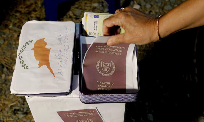 A demonstrator takes a  mock copy of Cyprus passport during a demonstration against corruption outside of the conference center in the capital Nicosia, Cyprus, on Oct. 14, 2020. (Petros Karadjias/AP Photo)