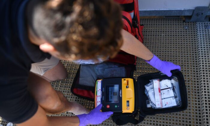 RNLI lifeguard supervisor Sam Woodard checks a defibrillator as he prepares a lifeguard station on the beach at Viking Bay in Broadstairs, south-east England, on May 28, 2020, during the COVID-19 pandemic. (Ben Stansall/AFP via Getty Images)