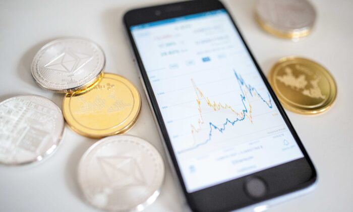 In this photo illustration of the litecoin, ripple, and ethereum cryptocurrency 'altcoins' sit beside a smartphone displaying the current price chart for ethereum, in London, England, on April 25, 2018. (Jack Taylor/Getty Images)