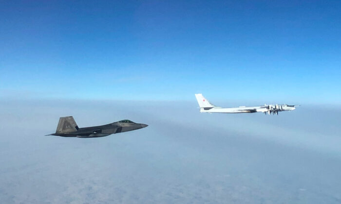 "An F-22 ""Raptor"" fighter jet (under) intercepts a Russian Tu-95 bomber after it entered the Alaskan Air Defense Identification Zone on Oct. 19, 2020. (NORAD)"