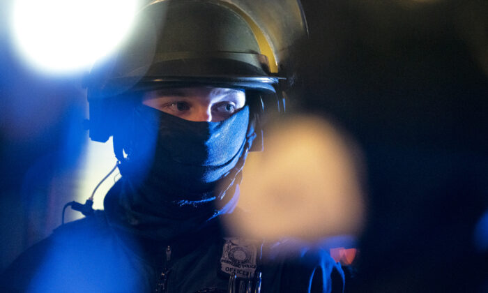 A Portland police officer monitors a group of protesters in Portland, Ore., on Oct. 7, 2020. (Nathan Howard/Getty Images)