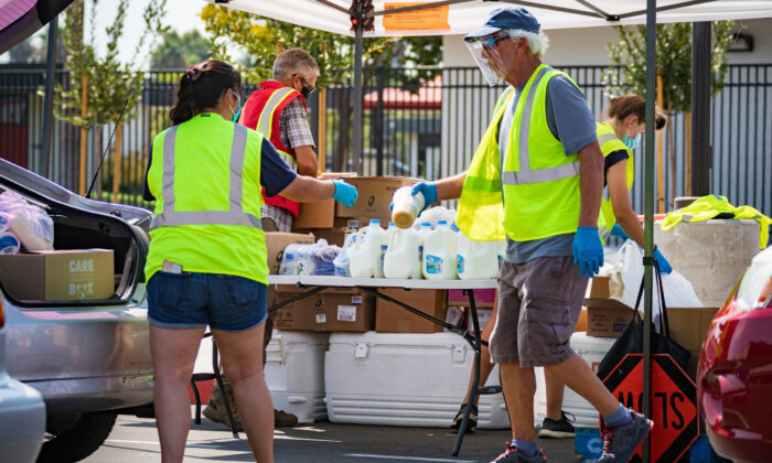 Volunteers distribute food to the needy at a drive-thru food pantry run by Saddleback Church in Anaheim, Calif., on Aug. 18, 2020. (John Fredricks/The Epoch Times)