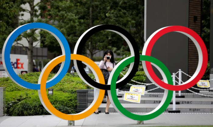 A woman wearing a protective mask takes a picture of the Olympic rings in front of the National Stadium in Tokyo, on Oct. 14, 2020. (Kim Kyung-Hoon/Reuters)