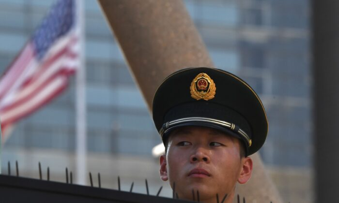 A paramilitary policeman looks on past the US flag on the embassy compounds in Beijing on July 26, 2018, following a blast near the US embassy premises. (Greg Baker/AFP via Getty Images)