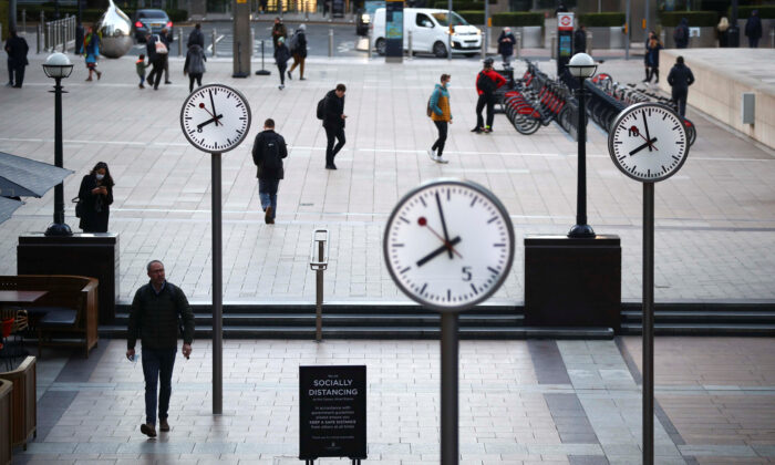 People walk during the morning rush hour in Canary Wharf amid the outbreak of the CCP virus in London on Oct. 15, 2020. (Reuters/Hannah McKay)