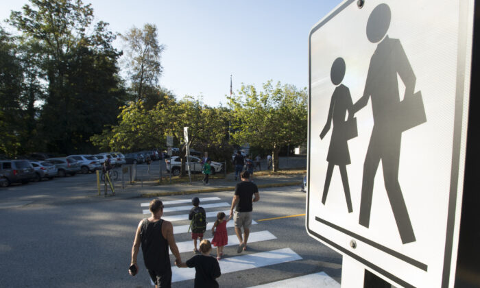 Parents walk their children to school in North Vancouver on Sept. 10, 2020.  (The Canadian Press/Jonathan Hayward)