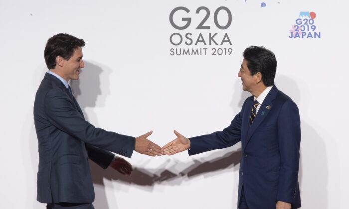 Japanese Prime Minister Shinzo Abe welcomes Canadian Prime Minister Justin Trudeau during the official welcome ceremony at the G20 Summit in Osaka, Japan, on June 28, 2019. Foreign policy experts agree Canada needs to forge closer ties with Japan as part of being more involved in the Indo-Pacific region. (The Canadian Press/Adrian Wyld)