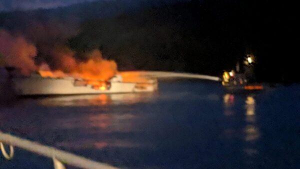 Firefighters work to extinguish a dive boat