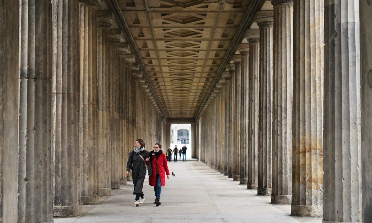 People walk through a colonade in the Museums Island