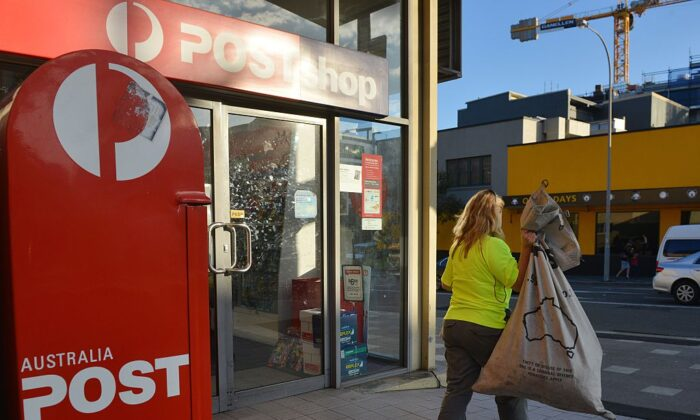 A worker carries a sack of letters after emptying a post box outside an Australia Post office in Sydney on June 26, 2015. (Peter Parks/AFP via Getty Images)