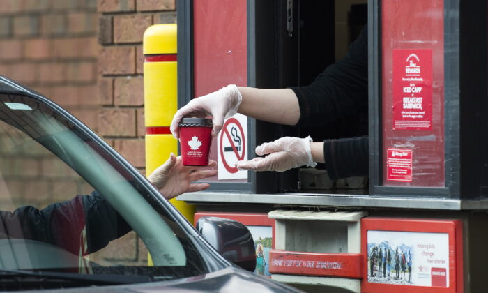 A Tim Hortons employee hands out coffee from a drive-through window to a customer in Mississauga, Ont., March 17, 2020. (The Canadian Press/Nathan Denette)